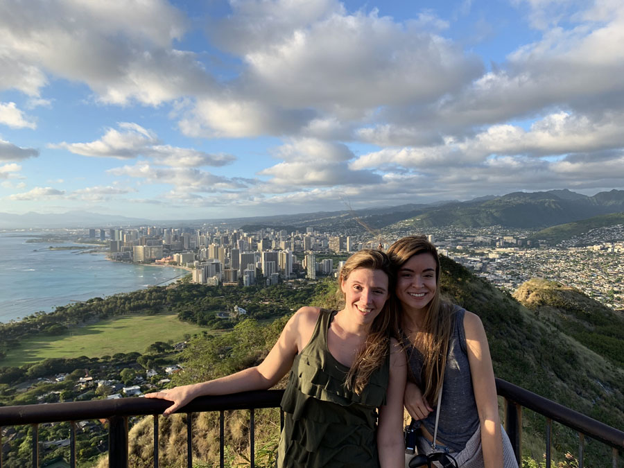 Two women posing on an overlook at the top of the Diamond Head Hike with Honolulu in the background
