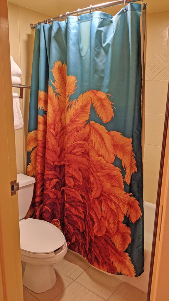 Carnival themed shower curtain in a guest bathroom at Disney's Caribbean Beach Resort