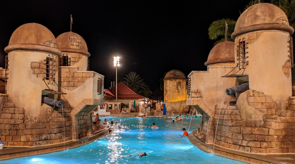 Swimmers near artificial fort towers at the Fuentes del Morro pool in Disney's Caribbean Beach Resort