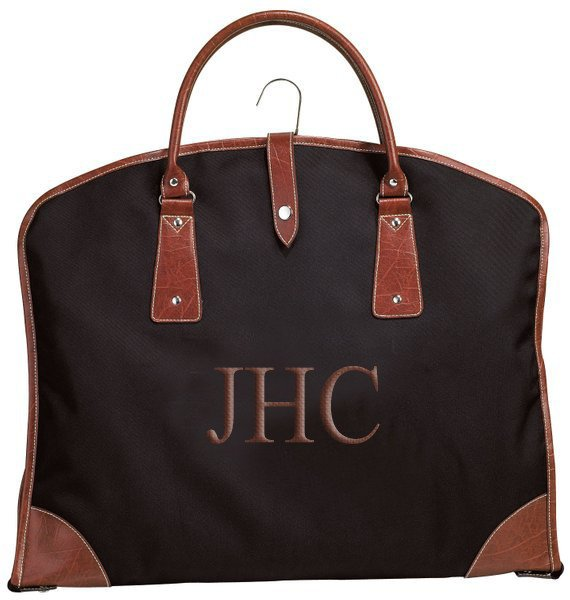 Black garment bag with brown leather trip and monogram