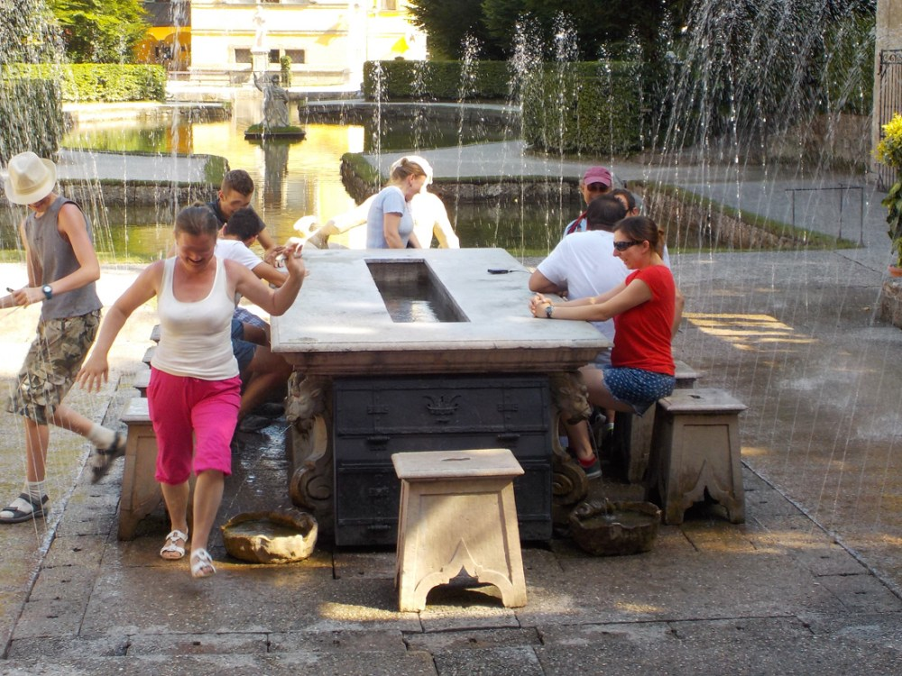 Outdoor table with trick fountains and guests fleeing from the water