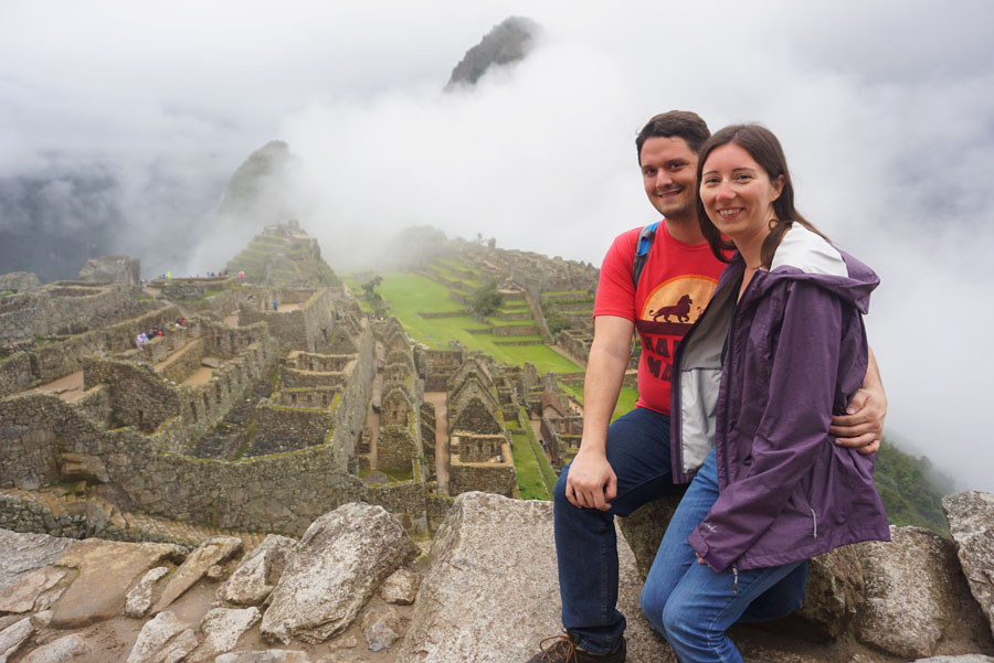 Man and woman posing in front of the Machu Picchu ruins