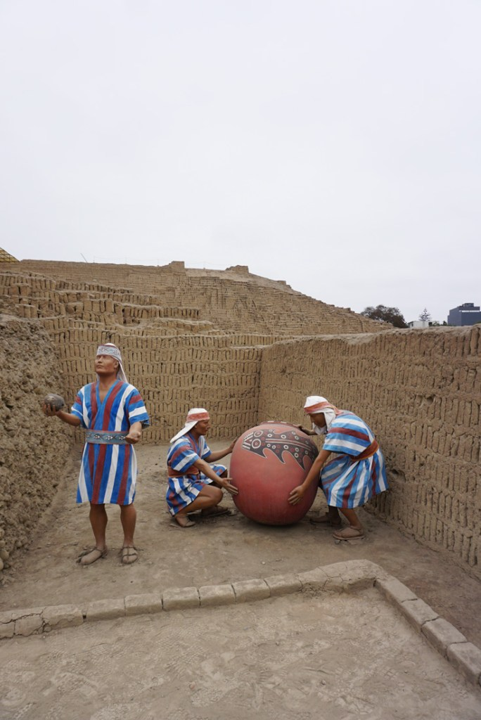 Statues showing a ceremonial offering during a Huaca Pucllana tour.
