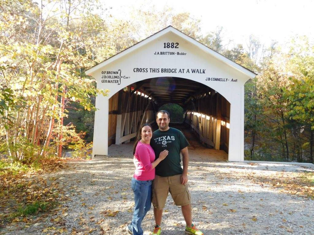 Couple posing in front of historic covered bridge