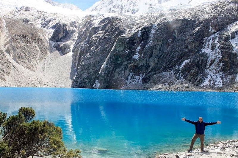 Hiker posing in front of Laguna 69 in Peru
