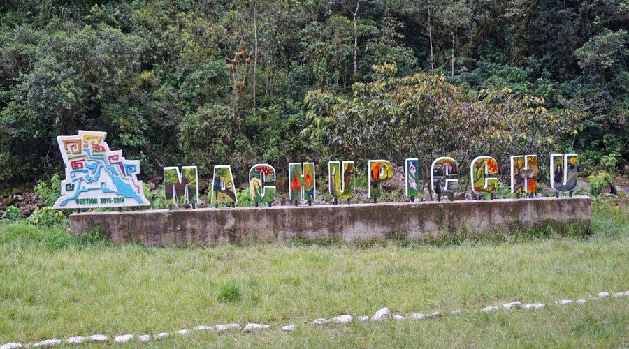 "Colorful sign reading ""Machu Picchu"" along the train to Aguas Calientes"