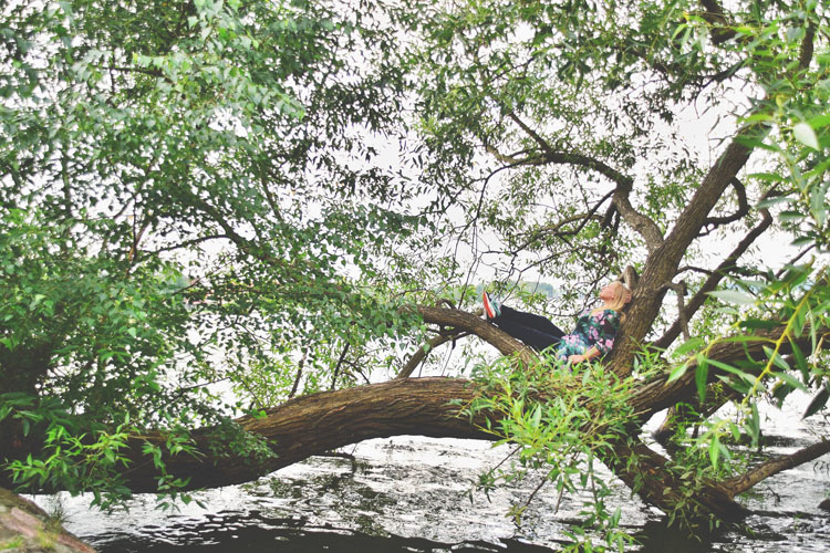 Woman relaxing in a tree in the Masurian Lake Region