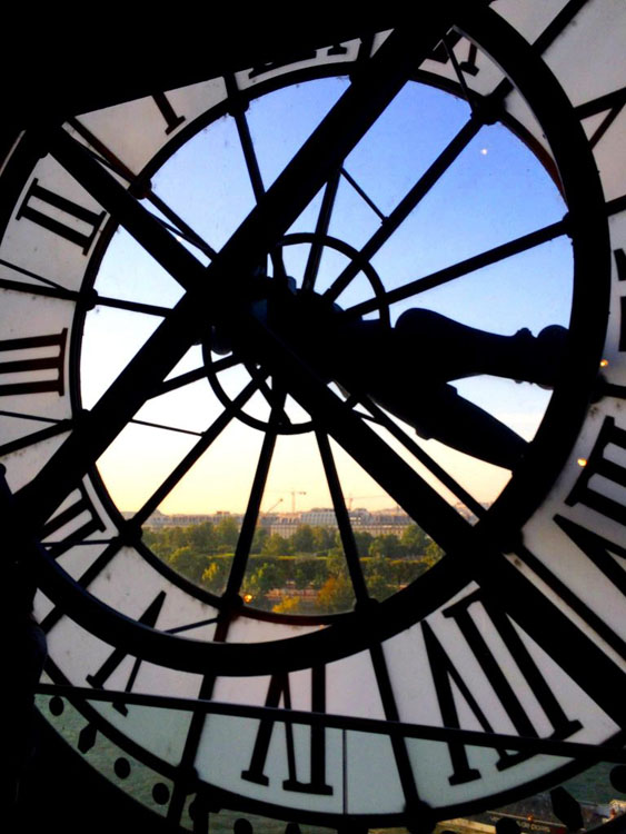 View of sunset over Paris through the glass in the giant clock at the Musee d'Orsay