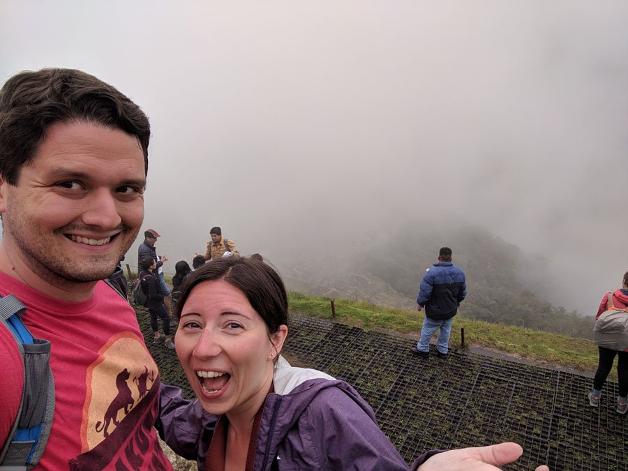 Man and woman laughing in front of a wall of fog