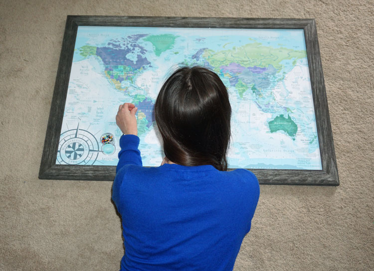 Woman in blue placing pins in a pushpin world map