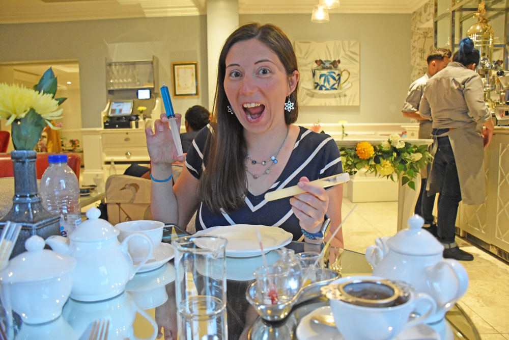 Woman holding a syringe of lemonade at the Science Afternoon Tea in London