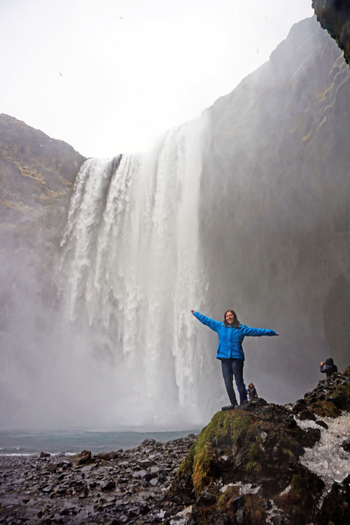 Woman posing in front of Skogafoss, high on the list of what to do in Iceland