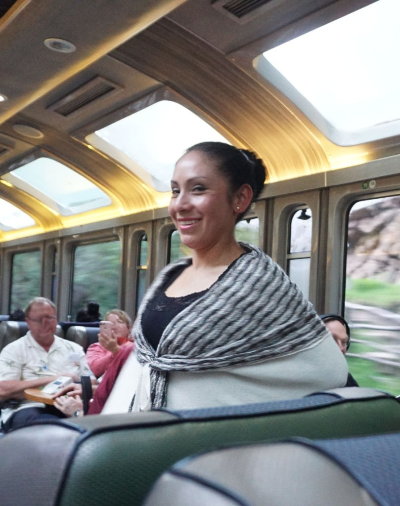 Young woman modeling Peruvian alpaca wool clothing on the train to Cusco