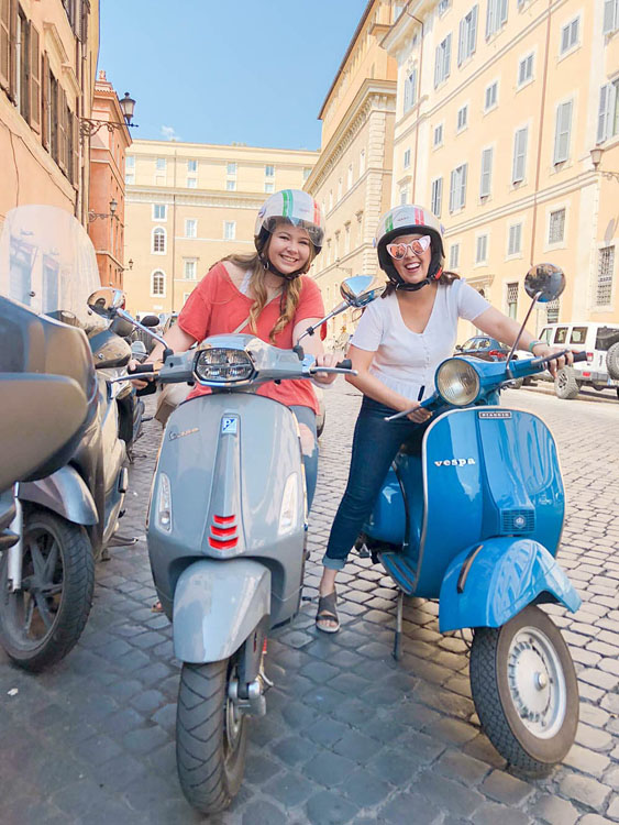 Riders on a Vespa tour of Rome, Italy