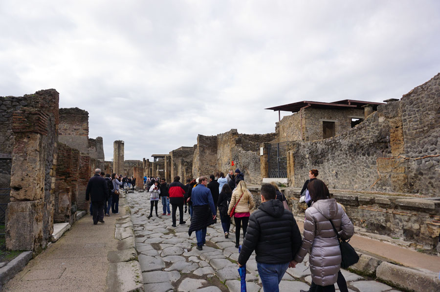 Tourists walking on cobblestone streets amid ruins on one of the many Pompeii tours available.