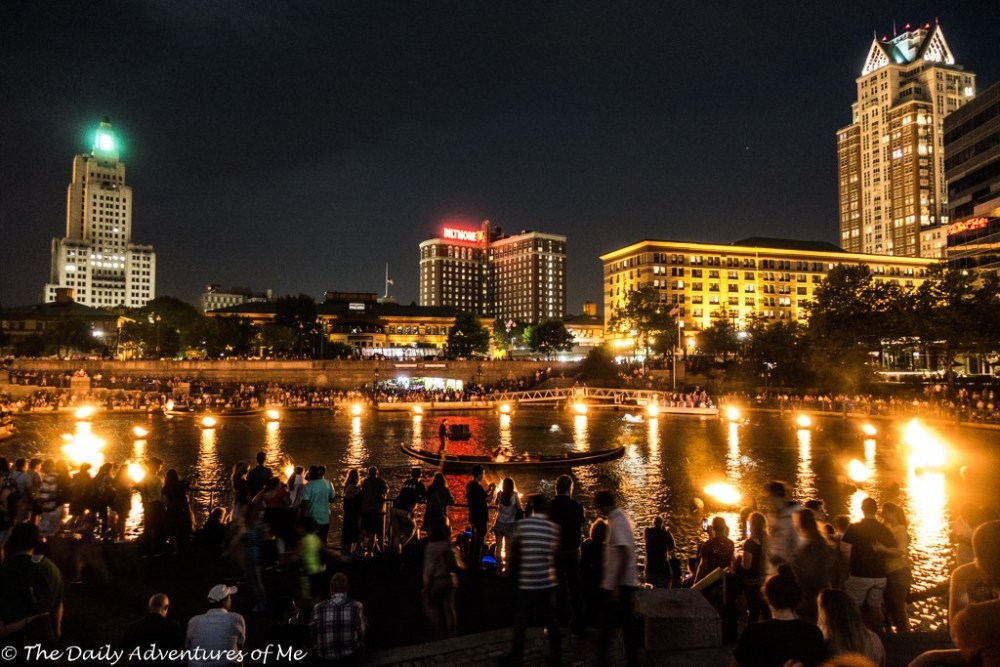 Boats floating among burning wood in WaterFire