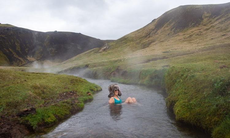 Woman in a fuzzy hat in the Reykjadalur thermal river in Iceland