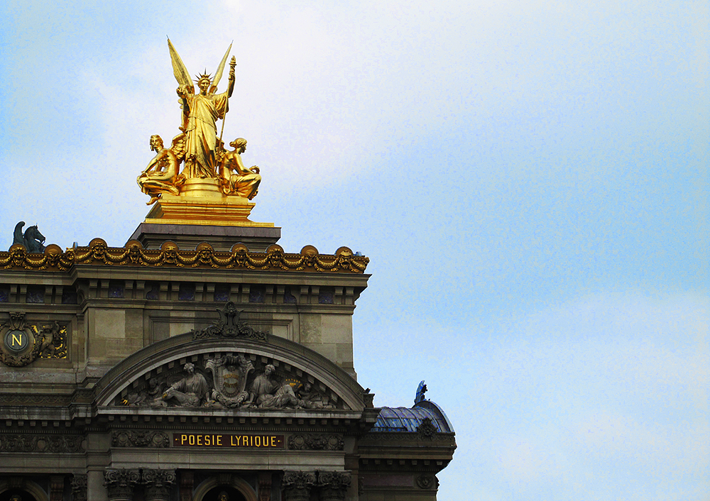 A corner of the Palais Garnier roofline against a blue Paris sky.