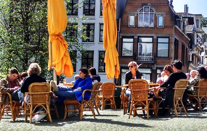 People at a terrace cafe in the sun in Amsterdam