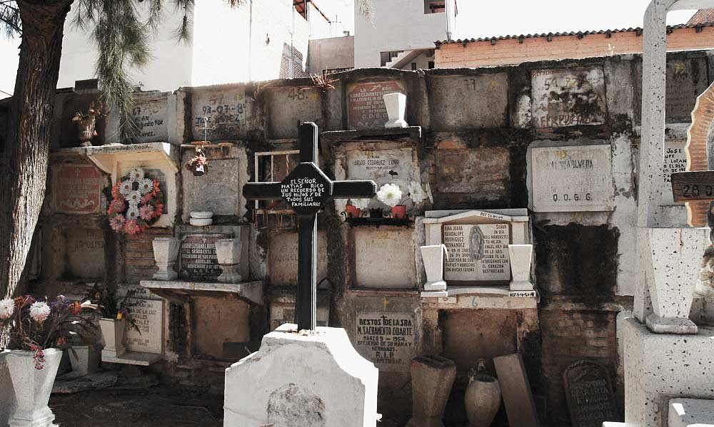 Nichos for urns, graves, a cross, plastic flowers, and the windows of people's homes overlooking the whole thing -- a glimpse of a typical Mexican cemetery in San Miguel de Allende, Guanajuato.