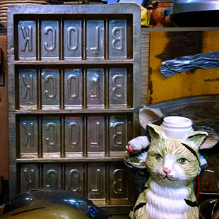 A metal chocolate bar mold shares a table with a ceramic cat.