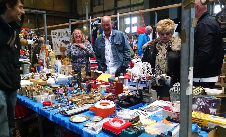 Vendors and eclectic goods at Amsterdam's IJ-Hallen flea market.