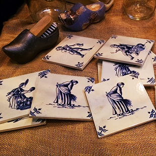Blue-and-white Delft tiles and black wooden shoes sit on a table.
