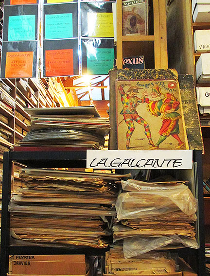 Stacks of bagged magazines, books and some old film canisters on a table at la Galcante.