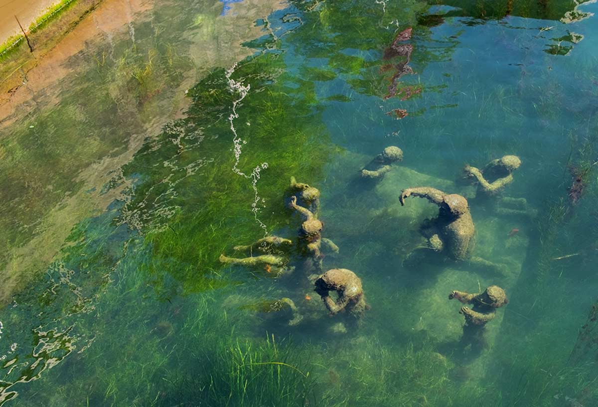 Another view of the sculptural grouping by Danish aartist Suste Bonnen of Agnete and the Merman--minus Agnete--with long grasses and moss waving in the blue-green water around their feet.