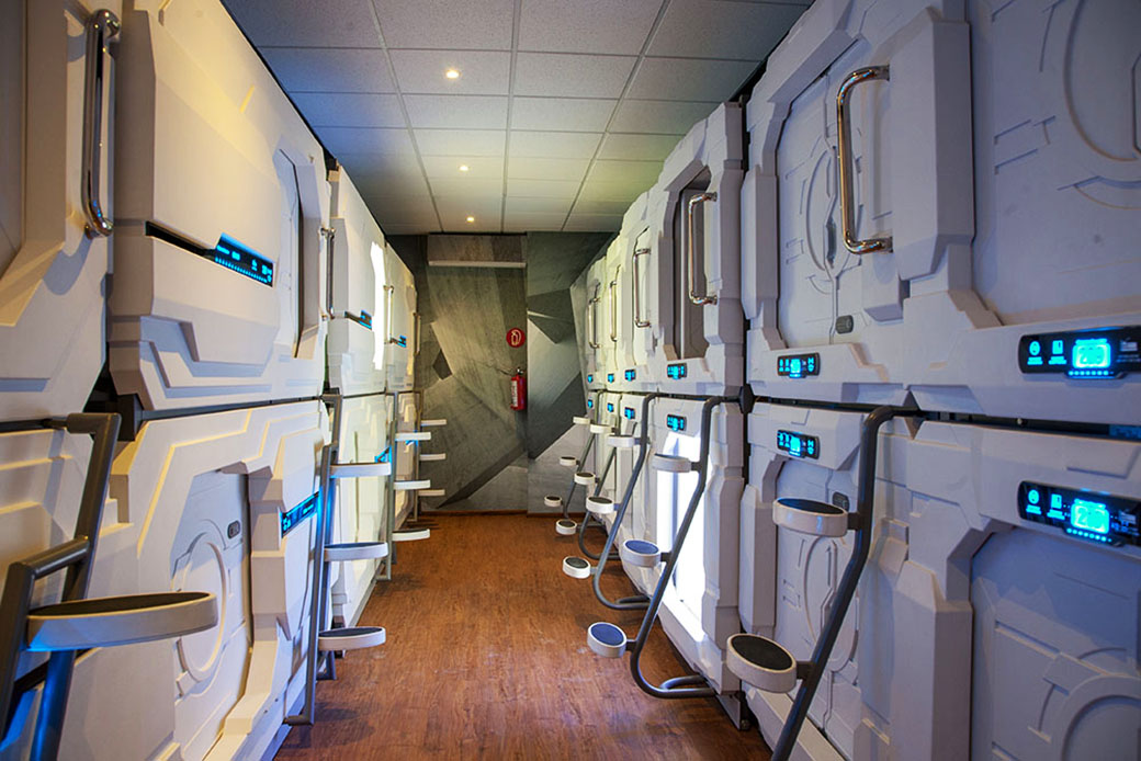 A look into the capsule/pod area at Izzzleep Capsule Hotel, showing the two levels of pods and the steps to ge to the upper-level pods.