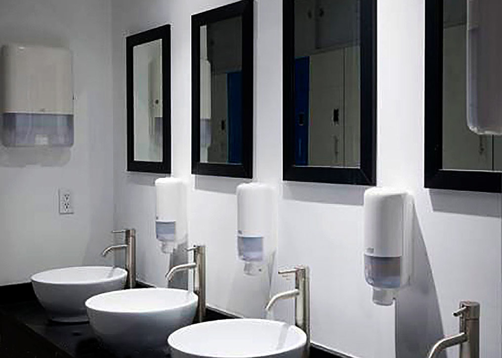 The row of modern sinks and mirrors is used communally and is co-ed.