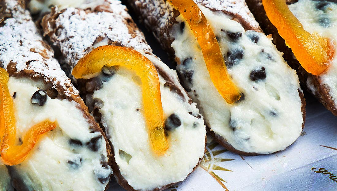 Cannoli, filled with sweetened ricotta with chocolate chips and disted with powdered sugar--a delicious Sicilian dessert