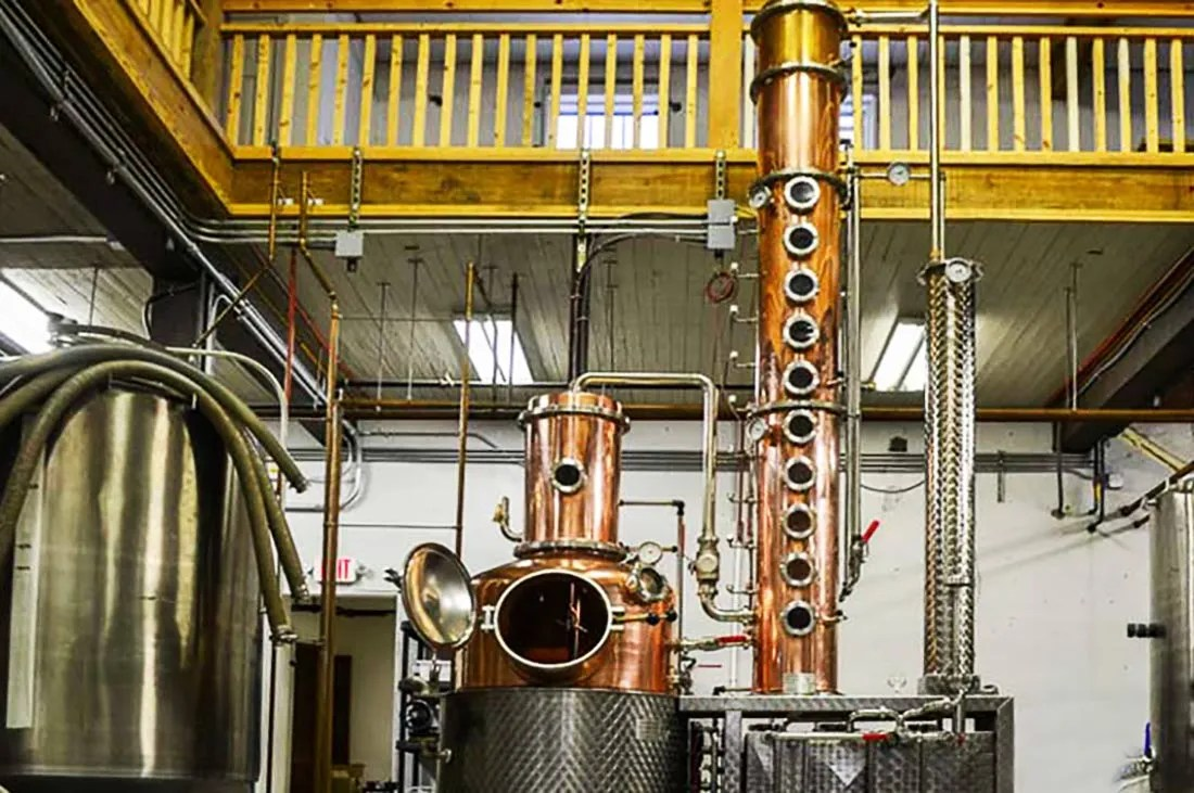 The 300-liter copper pot still from Outer Banks Distilling looks like a giant copper oboe in a stainless steel tube.