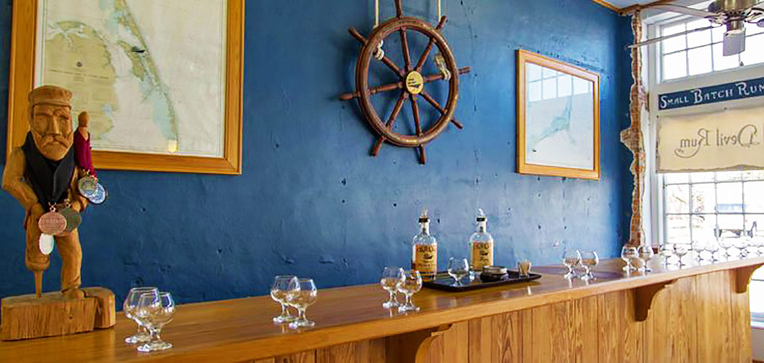"The ship's wheel from the wrecked schooner ""Irma"" hangs on the wall of the tasting room at Outer Banks Distilling."