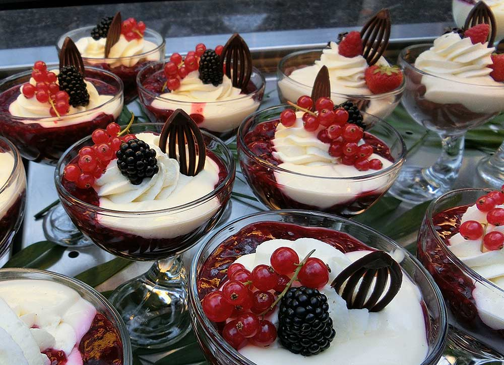 Servings of very berry Rote Grutze, topped with whipped cream and a chocolate garnish--a traditional German dessert