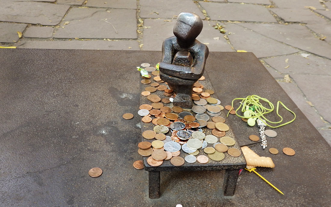 Järnpojke, Iron boy, sits on a small iron table covered with coins from many nations, candy, flowers, and other gifts to bring luck.