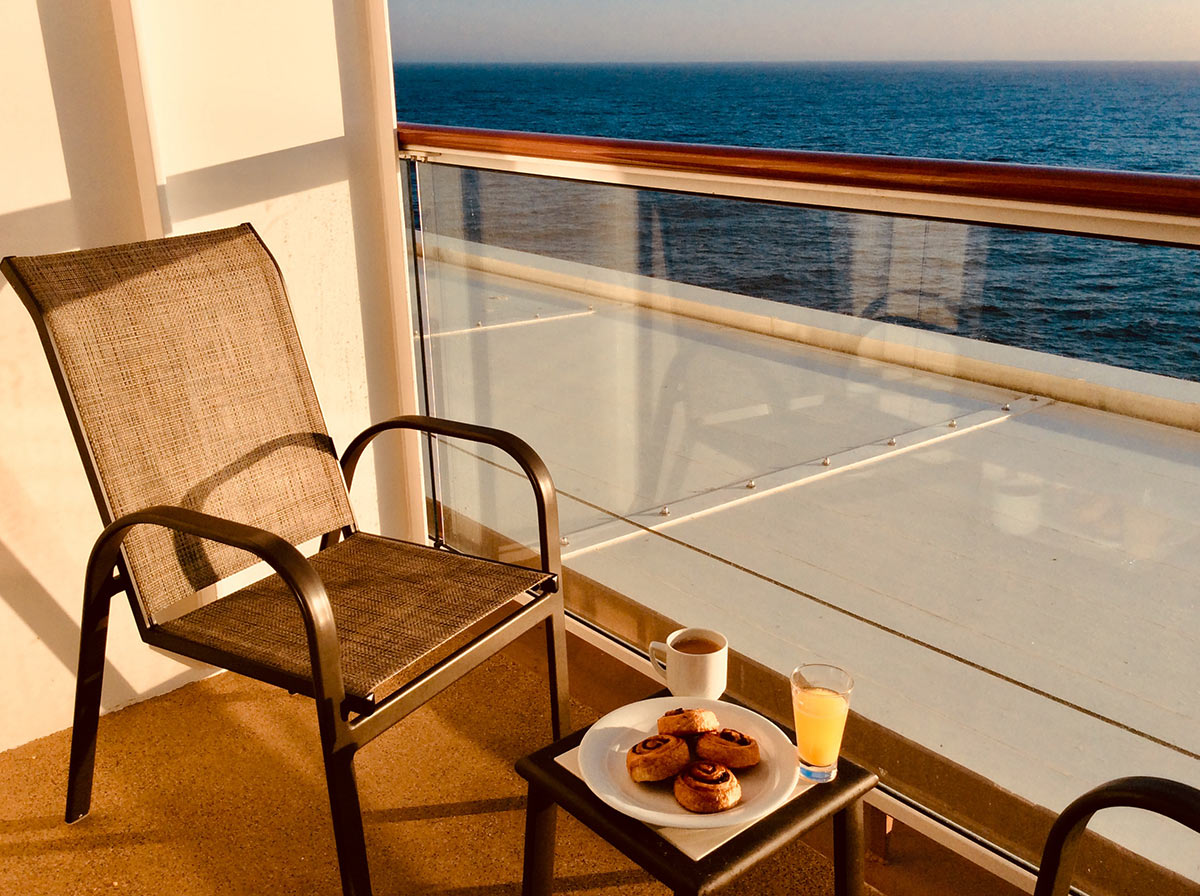 Our petite balcony on the Norwegian Joy cruise ship, with an armchair, a tiny table with coffee and pastries, and the open sea beyond. Morning Coffee.