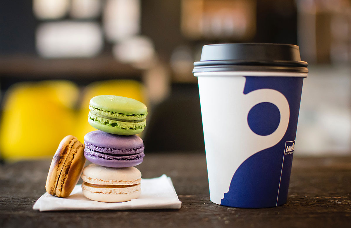 A lidded go-cup and a pile of colorful French macarons.