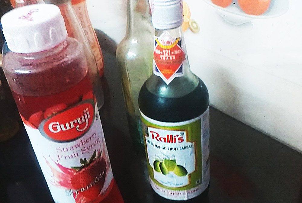 Glass bottles of strawberry and green mango syrup, ready to mix into refreshing fruit drinks in India.