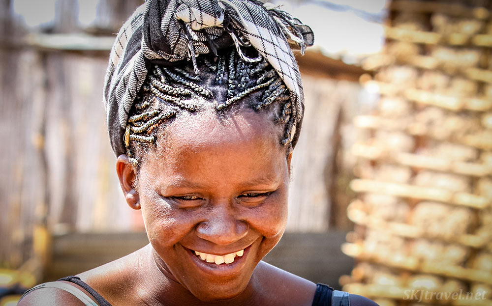 A woman in Namibia with tightly braided hair wrapped in a scarf. And a beautiful smile.