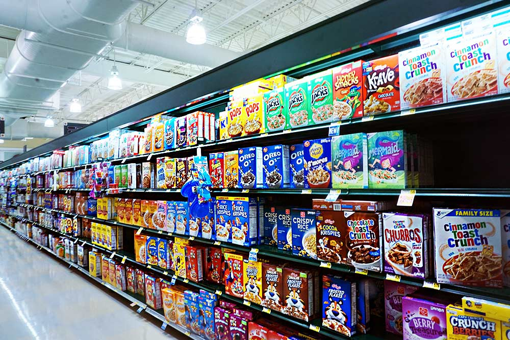A very, very long supermarket aisle in the U.S. stacked with dozens of types and flavors of dry cereal.