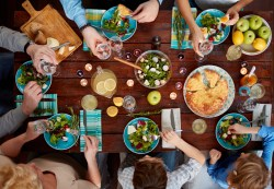 Multi-generation family having a delicious dinner with starters and courses - aerial shot