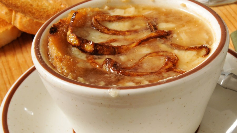 caramelized onions in A cup of French Onion soup with toast and gruyere cheese