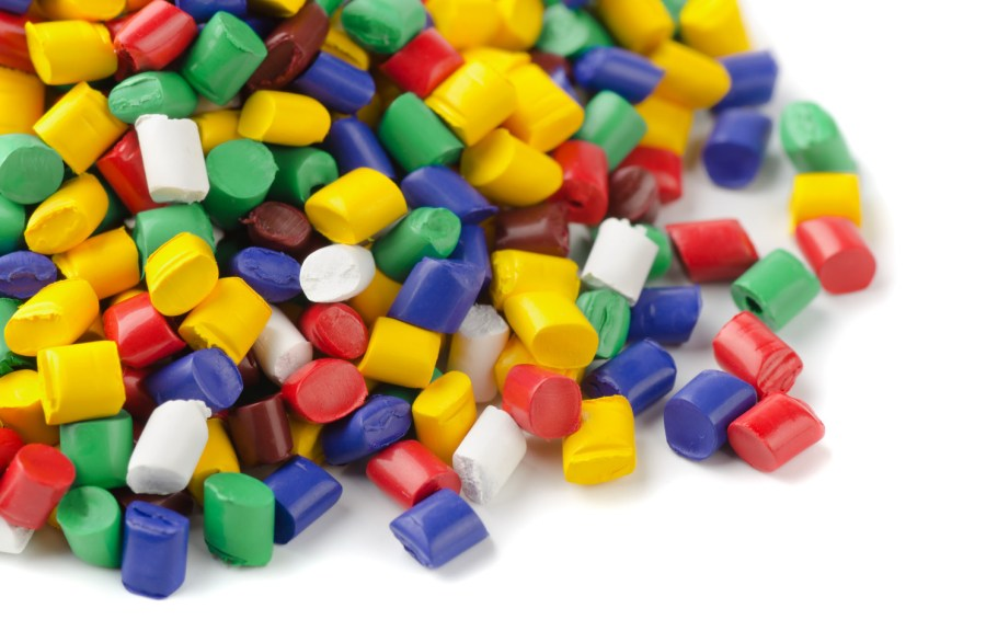 plastic handlesssors made them light and colorful - on a pair of sciColourful plastic polymer granules on white