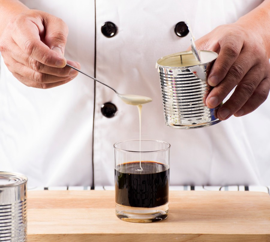 Chef putting sweetened condensed milk in to Hot coffee