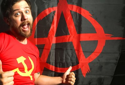 The author in a sickle and flag shirt standing in front of an anarchism flag.