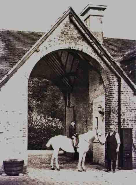The stable yard entrance before the Great War. The boy on the horse is believed to be the late John Plumptre, who died in 1987.