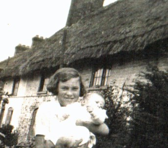 Mrs. Kath Smith, née Harrison, at the front of the cottages which overlooked the cottage gardens.