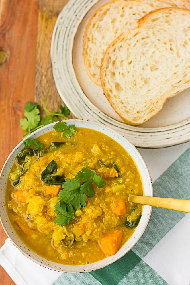 cauliflower sweet potato curry soup with a side of bread.