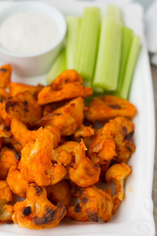 Cauliflower Buffalo wings with celery and ranch on a plate.